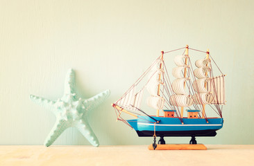 decorative boat and seashell over wooden textured background.