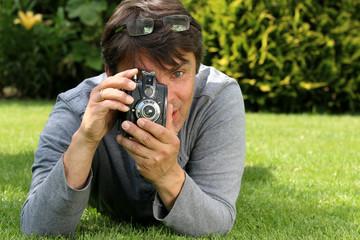 Mann macht mit alter Boxkamera Foto im Garten