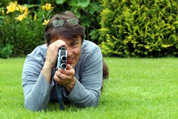 Mann im Garten lächelt, filmt mit alter Kamera