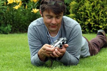 Mann liegt auf Wiese schaut auf alte Filmkamera