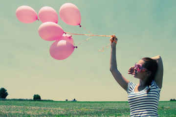 Young woman holding pink balloons and flying over a meadow. Phot