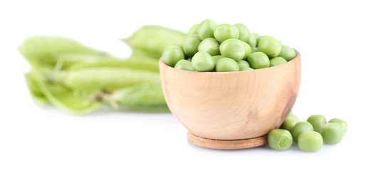 Fresh green peas in wooden bowl, isolated on white background