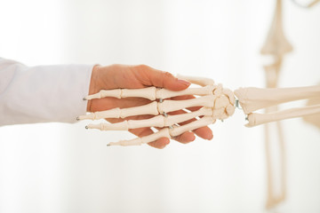 Closeup on medical doctor woman shaking hands of skeleton