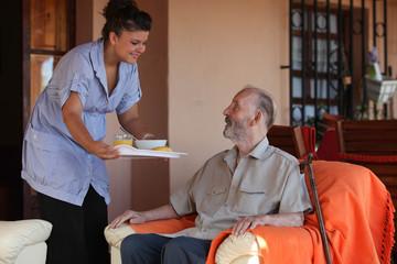 nurse or helper in residential home giving food to senior man