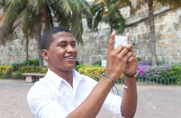 Attractive guy taking a picture with phone