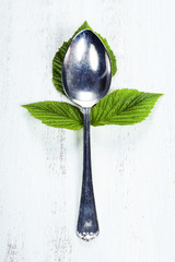 Spoon with fresh leaves. Health, diet, vegetarian food concept