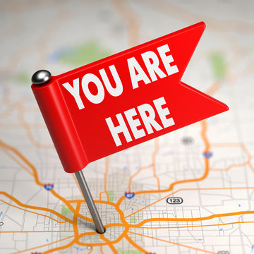 You Are Here - Small Flag on a Map Background.