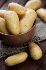 Close-up of raw potato in a glass bowl, vertical shot