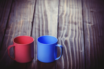Two color cups on wooden table.