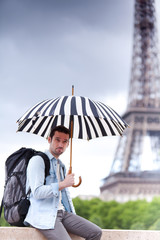 Young attractive man suffering rain in Paris