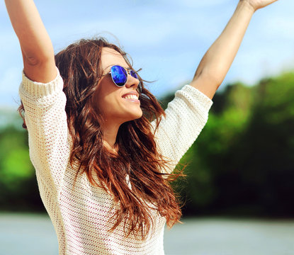 Attractive happy woman in sunglasses enjoying freedom outdoors w