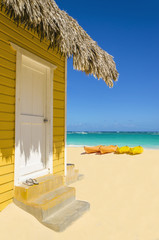 Wooden yellow beach cottage against colorful kayaks