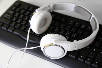 Headphone and keyboard close-up on white desk background