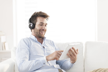 man  listening music with headphone and digital tablet