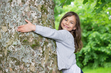 Little Girl holding big tree