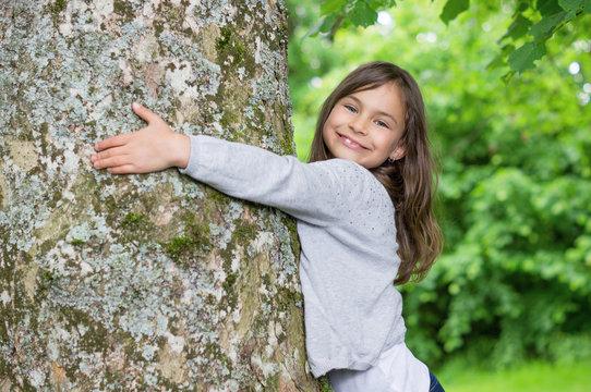 Little Girl holding big tree