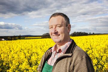 Farmer stands in rape field
