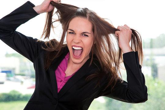 Junge Geschäftsfrau ist wütend und zieht an Haare