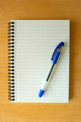 Notepad and Pen on Wooden Desk