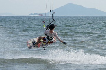 Male kite surfer jumping with ferry behind