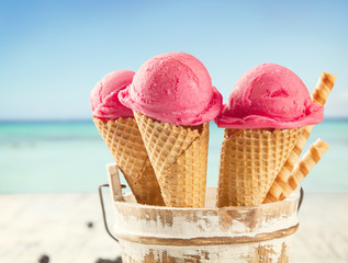Ice cream scoops in cones with blur beach