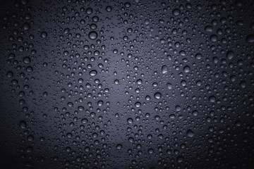 Water droplets on the glass with a colored background