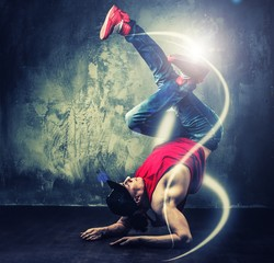 Stylish  break-dancer dancing with magic beams around him