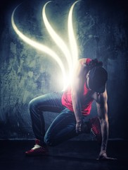 Stylish break-daner dancing with magic beams around him