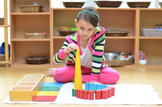 Little girl hand building tower made of blocks