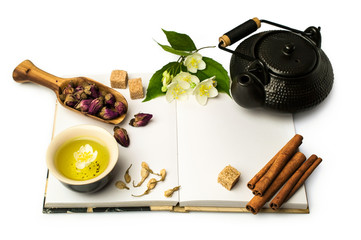 Open notebook and Asian tea set