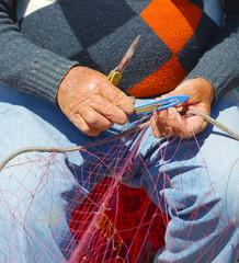 Fisherman is repairing the fishnet.