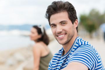 lächelnder junger mann sitzt am meer