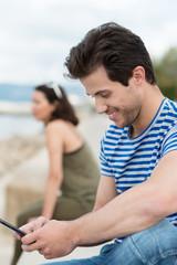 lächelnder junger mann schaut auf sein smartphone