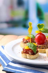Fototapete - Tasty canapes with salami,tomato, pepper  and basil leaves,