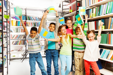 Happy children with hands up hold exercise books