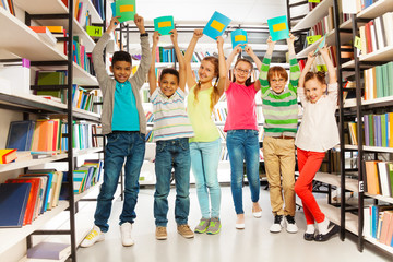 Six children with hands up hold exercise books