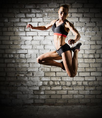 Muscular jumping woman on brick wall (dark version)