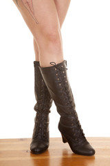 woman legs crossed stand boots tattoo