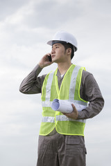 Asian industrial engineer at work using phone.