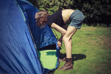 Young woman standing outside tent