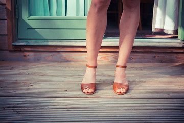 The legs of a woman standing on a porch