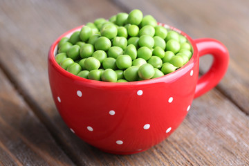 Green peas in red cup on wooden background
