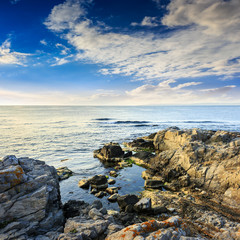 calm sea with boulders on coast
