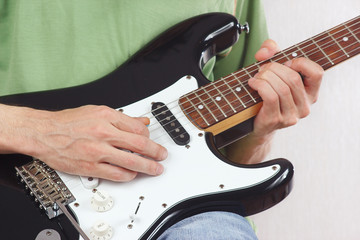 Posing hands of the rock musician playing the electric guitar