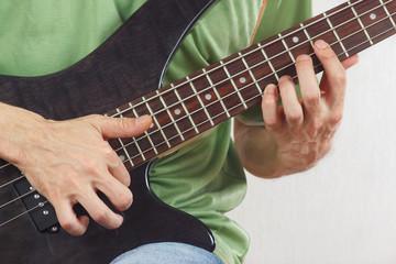 Hands of artist playing the electric bass guitar closeup