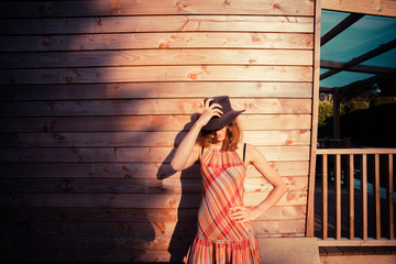 Young woman wearing cowboy hat by a cabin