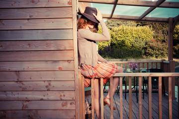 Woman wearing cowboy hat sitting on porch