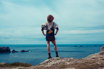 Young woman standing on a rock by the sea