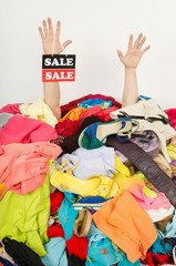 Man hands with sale sign reaching out from a big pile of clothes