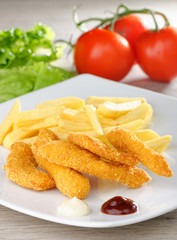 chicken nuggets/sticky fingers and french fries on a white plate